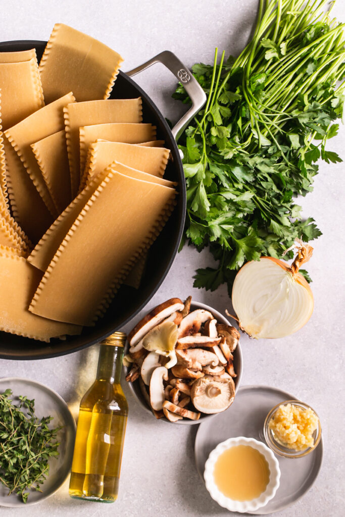 a stock pot with lasagna uncooked lasagna noodles, next to it fresh parsley, thyme, a bowl of lemon juice and minced garlic, a bowl of mushrooms and a bottle of white wine