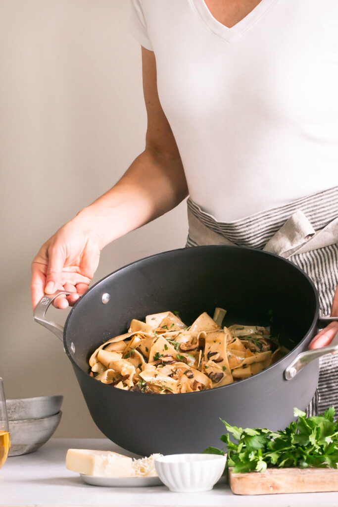 a woman holding a pot of Gluten-Free Pappardelle with Wild Mushroom Ragù with a cutting board with parsley on it, vegan parmesan cheese in front