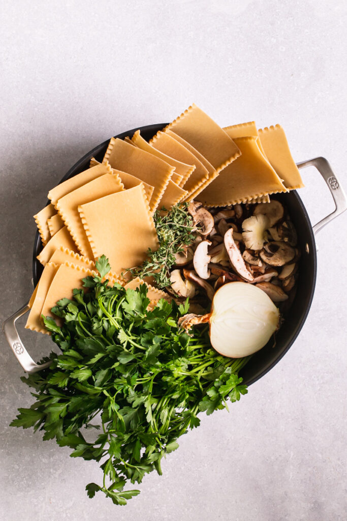 Calphalon Calphalon Premier™ Hard-Anodized Nonstick dutch oven with uncooked lasagna noodles, parsley, onion, mushrooms in it