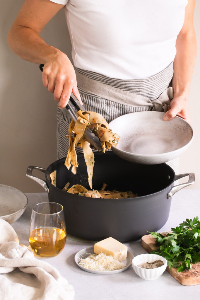 a woman with a pot of Gluten-Free Pappardelle with Wild Mushroom Ragù serving some into a bowl with tongs