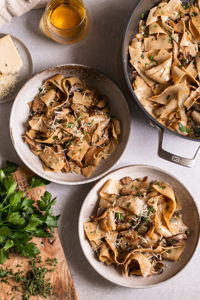 two bowls of gluten-free pappardelle with wild mushroom Ragù next to the serving pot of pasta, a glass of wine, and a cutting board with fresh parsley beside it