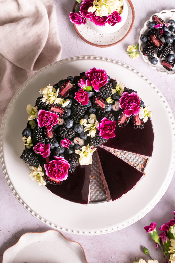 haskap berry cheesecake sliced on a cake platter topped with berries and flowers