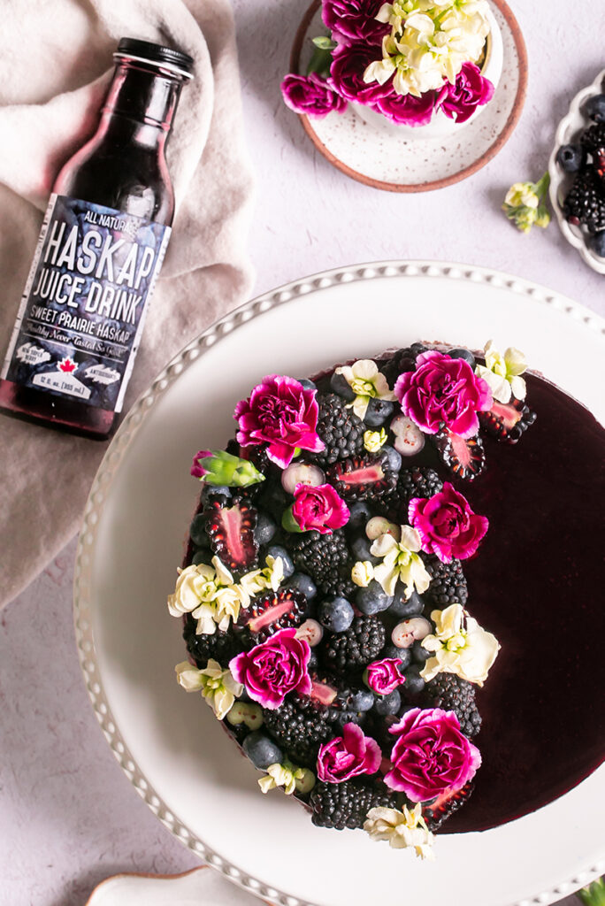 unsliced haskap berry cheesecake on a cake plate with a bottle of haskap berry juice next to it