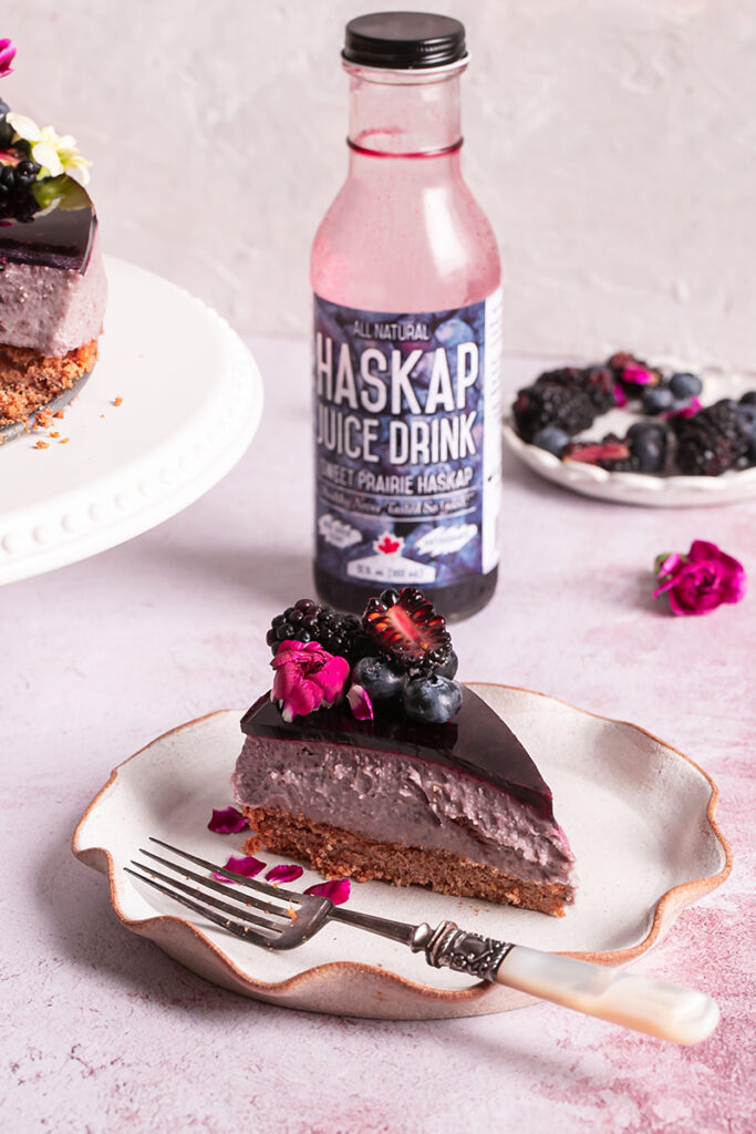 a slice of haskap berry cheesecake with a bottle of haskap juice in the background