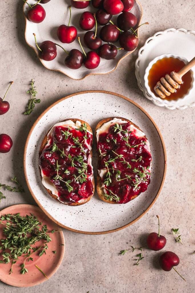 two slices of toast with dairy-free cream cheese, roasted cherries and fresh thyme on top and a plate of fresh thyme, a plate of fresh cherries, and a bowl of agave syrup around it