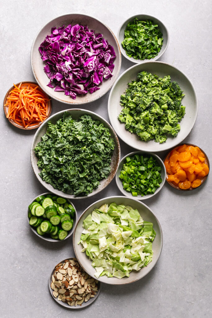 chopped kale, broccoli, red cabbage, green cabbage, green onion, cucumber, cilantro, sliced carrots, mandarine oranges and sliced almonds all in bowls