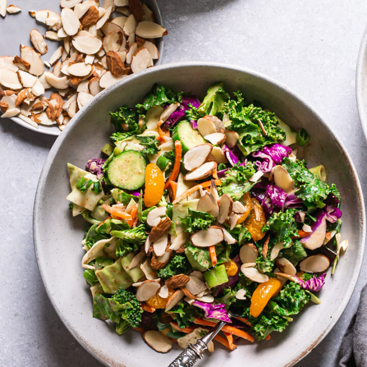 a bowl of Thai chopped salad with a fork in the bowl, a plate of sliced almonds and dressing next to the bowl