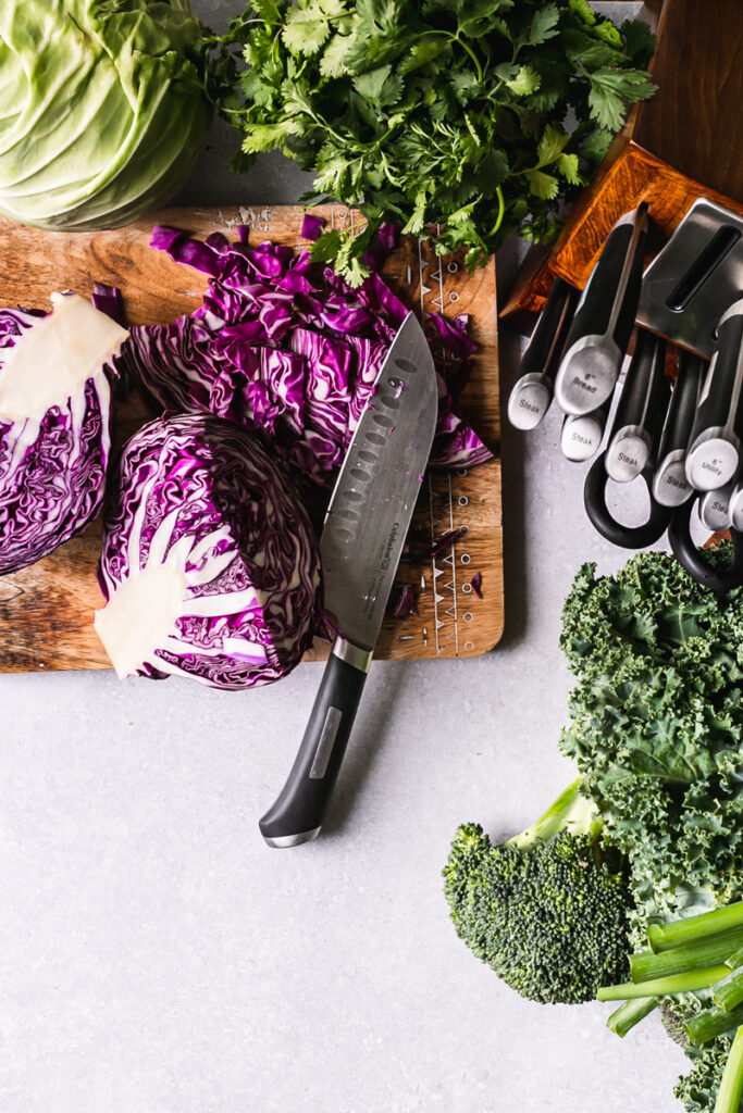fresh produce on a cutting board with a knife laid out on the cutting board chopping red cabbage and a block of calphalon knives on the side