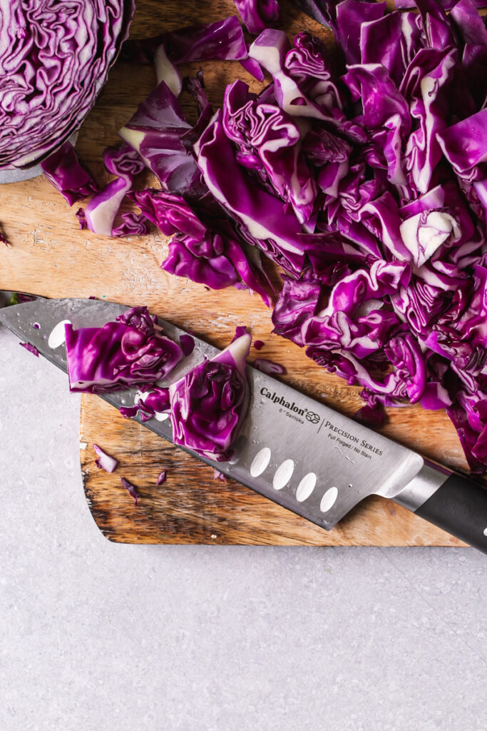 """Calphalon 6"""" santoku knife on a cutting board with chopped red cabbage"""