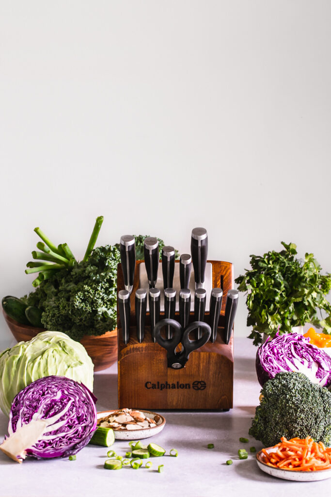 a block of Calphalon knives with fresh produce all around it