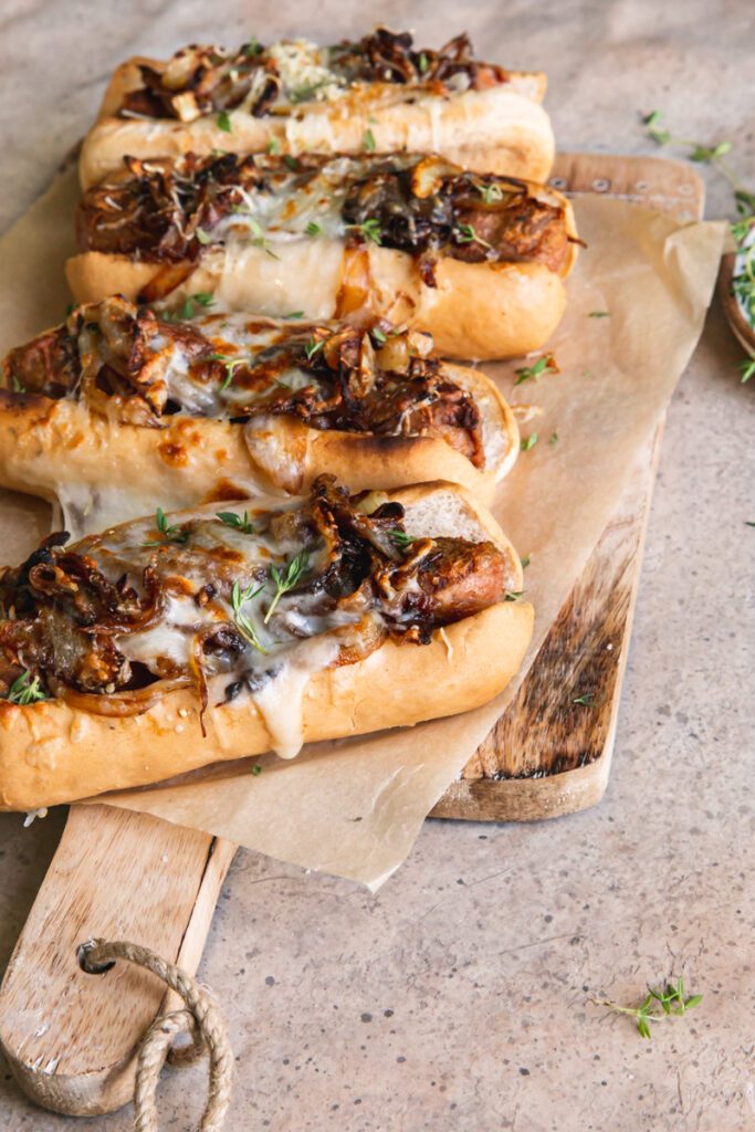 side view of vegan French onion brats on a parchment lined wooden cutting board