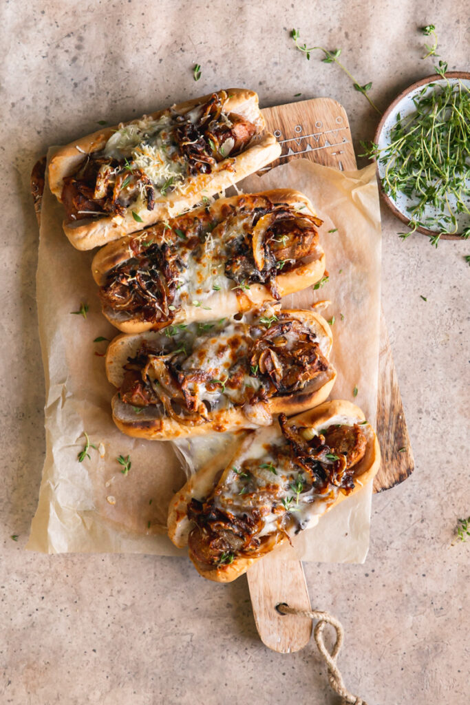 four vegan French onion brats layed out on a parchment line wooden cutting board with a bowl of fresh thyme next to it
