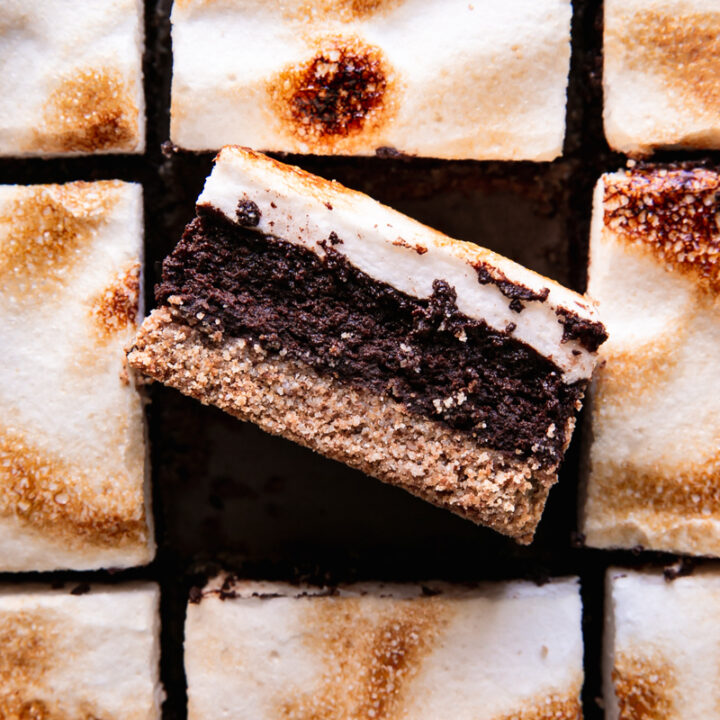 sliced s'mores brownies with toasted marshmallow fluff on top and the middle brownie on its side showing the brownie center and graham-style crust