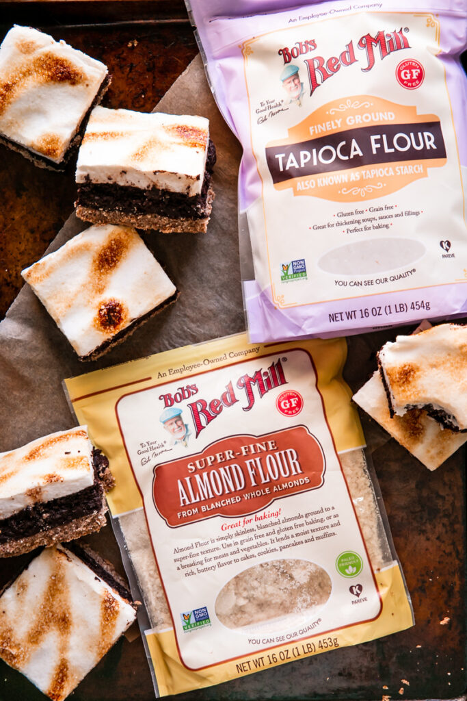 flatlay image of Bob's Red Mill Tapioca flour and almond flour with s'mores brownies all around it on a baking sheet