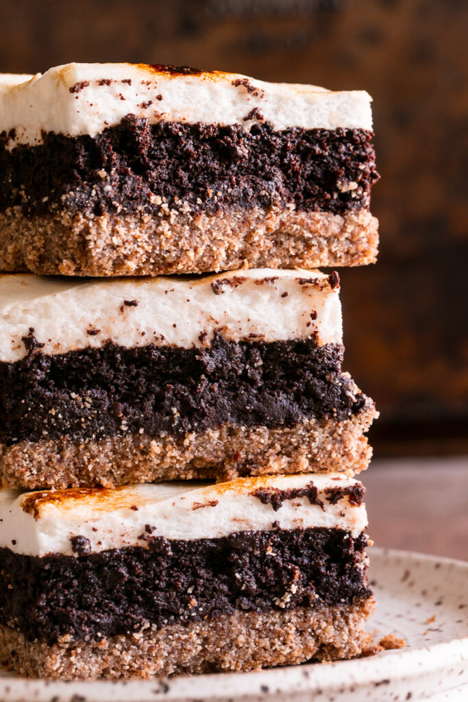 close up shot of three s'mores brownies stacked on top of one another on a plate