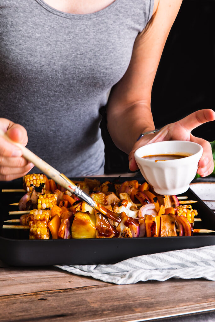 action shot of me bruising barbecue sauce over the kabobs in the Calphalon grill pan