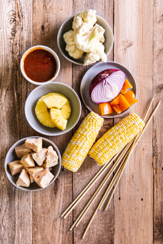 kabob ingredients all laid out- corn on the cob, jackfruit, pineapple, red onion, cauliflower, pepper, kabob sticks and homemade barbecue sauce