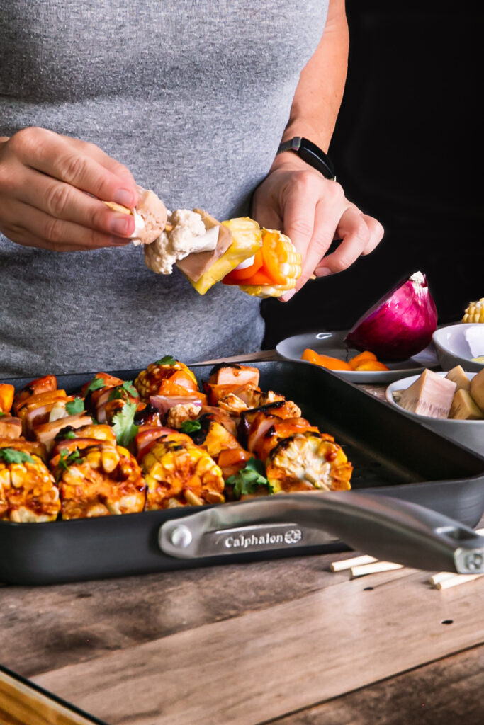 action shot of me placing the food on a kabob stick with the Calphalon grill pan  on the table in front of me and the ingredients beside me