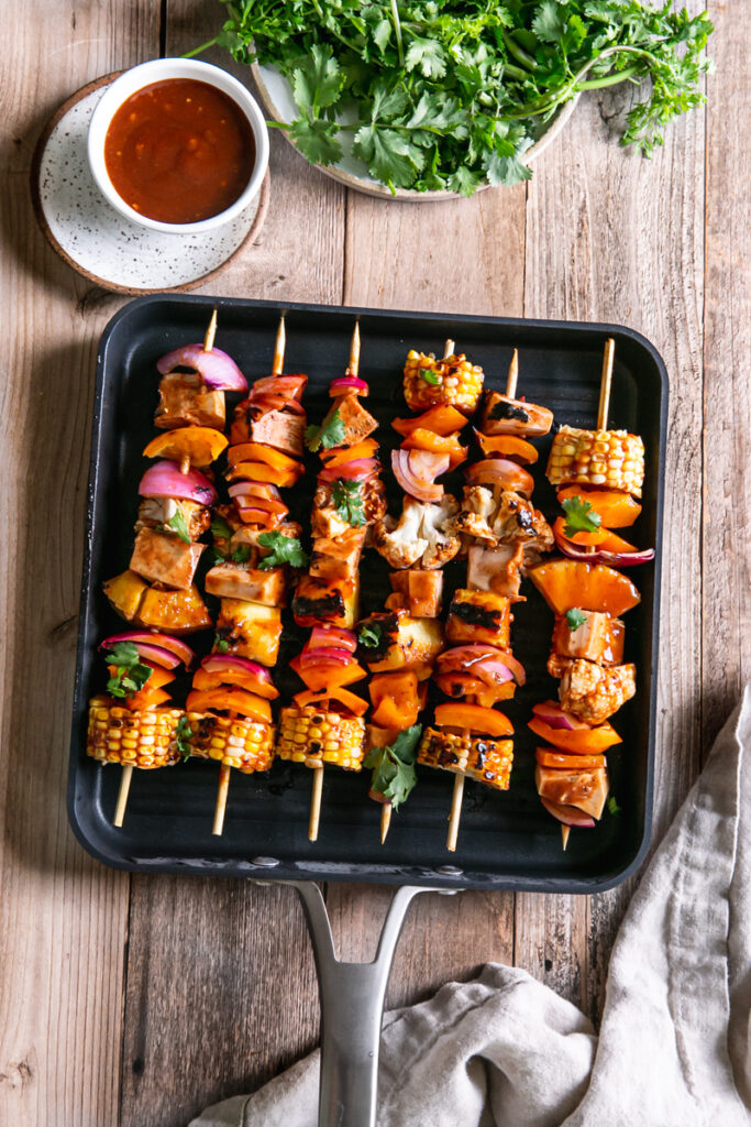 Grilled veggie barbecue jackfruit kabobs in a square Calphalon grilling pan with a bowl of barbecue sauce beside it and a plate of cilantro above it