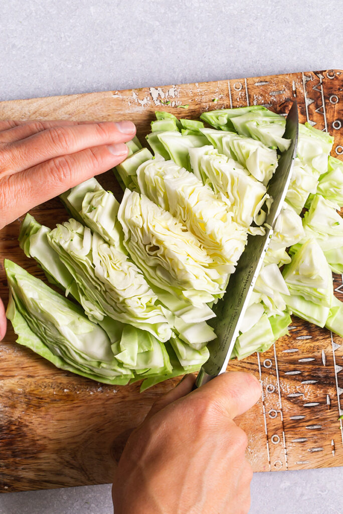 action shot of hands chopping green cabbage