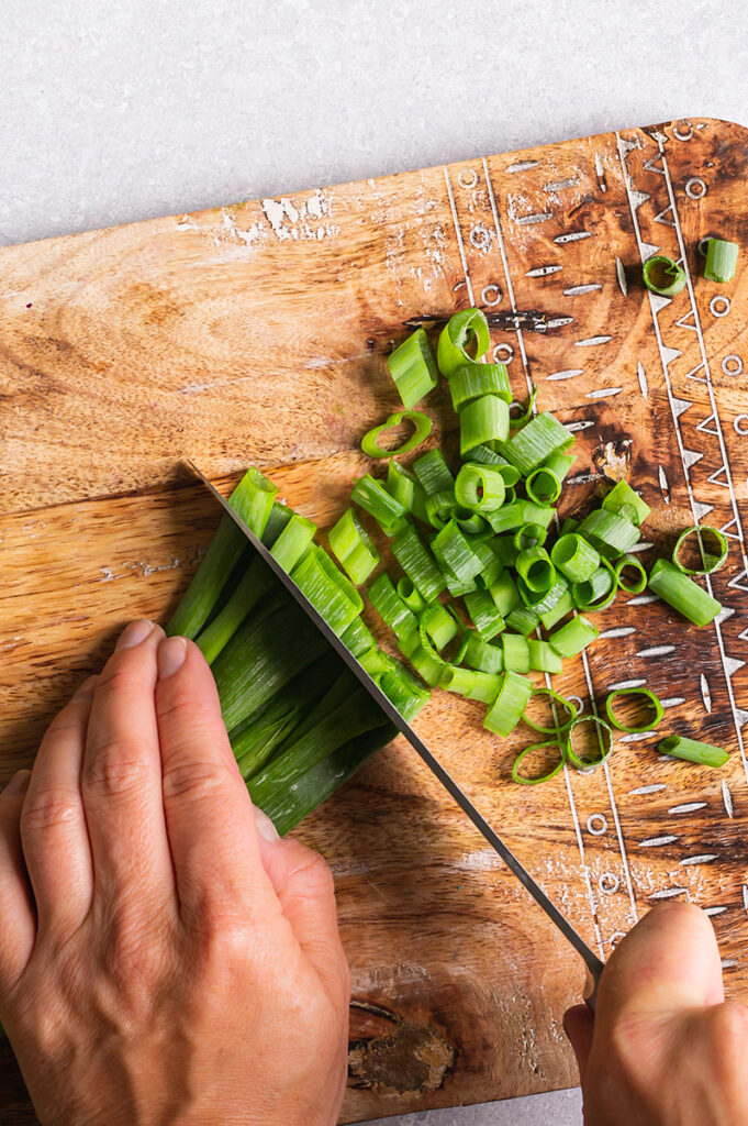 action shot of hands chopping green onions