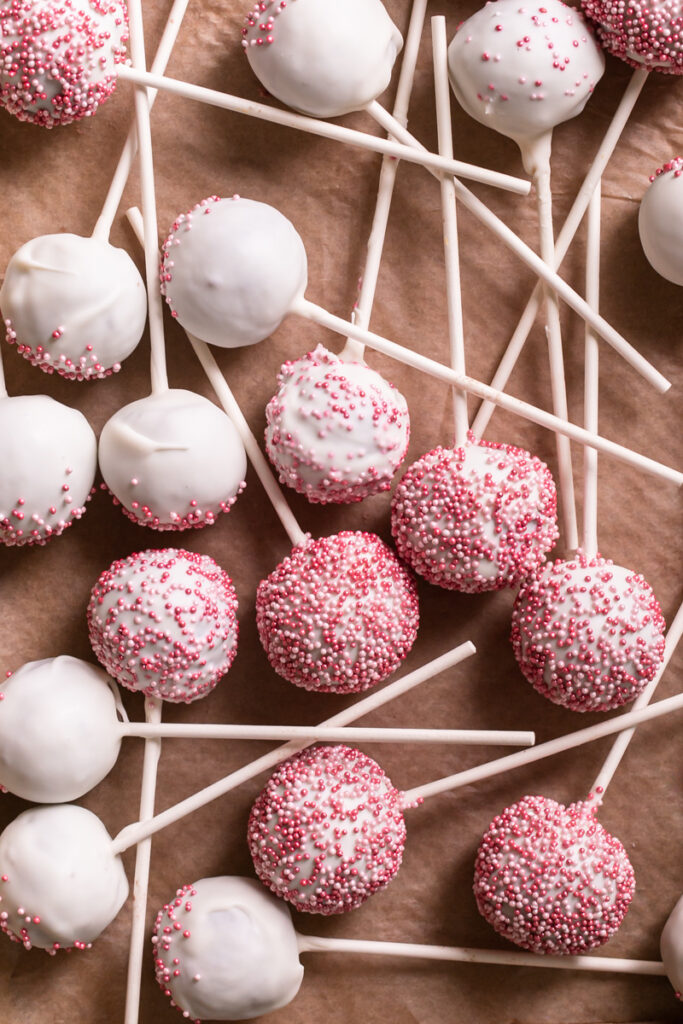 overhead shot of cherry cake pops layed out on a parchment-lined baking sheet