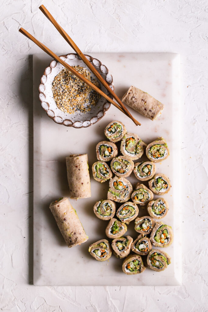a marble cutting board with 3 rolled up unsliced veggie sushi sandwiches and sliced rollup sandwiches with a bowl of everything bagel spice and wooden chopsticks