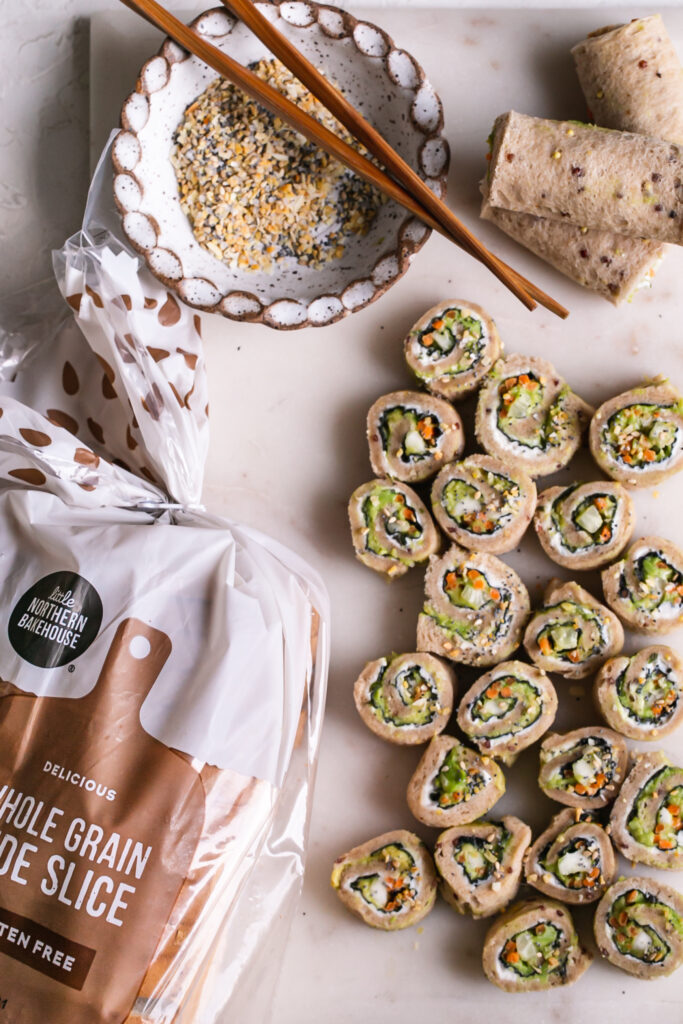 a marble cutting board with 3 rolled up unsliced veggie sushi sandwiches and sliced rollup sandwiches with a bowl of everything bagel spice and wooden chopsticks an a loaf of Little Northern Bakehouse whole grain bread