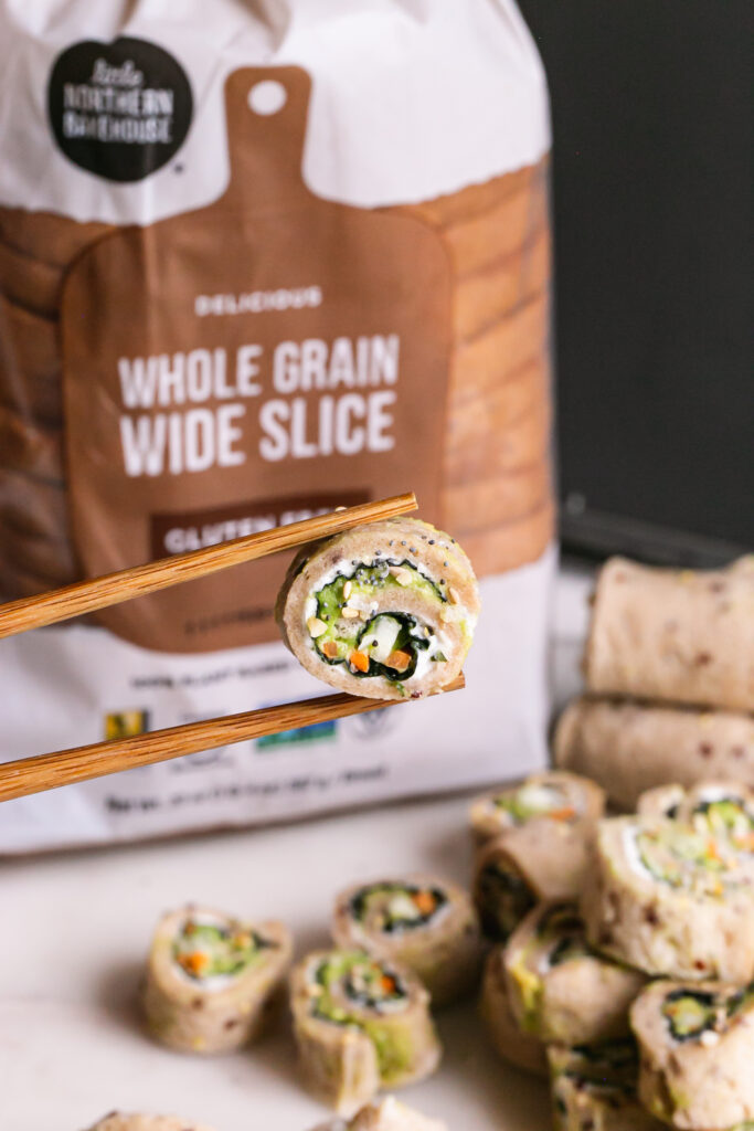 vertical image of a slice of veggie sandwich sushi held with chopsticks and a loaf of Little Northern Bakehouse whole grain bread in the background