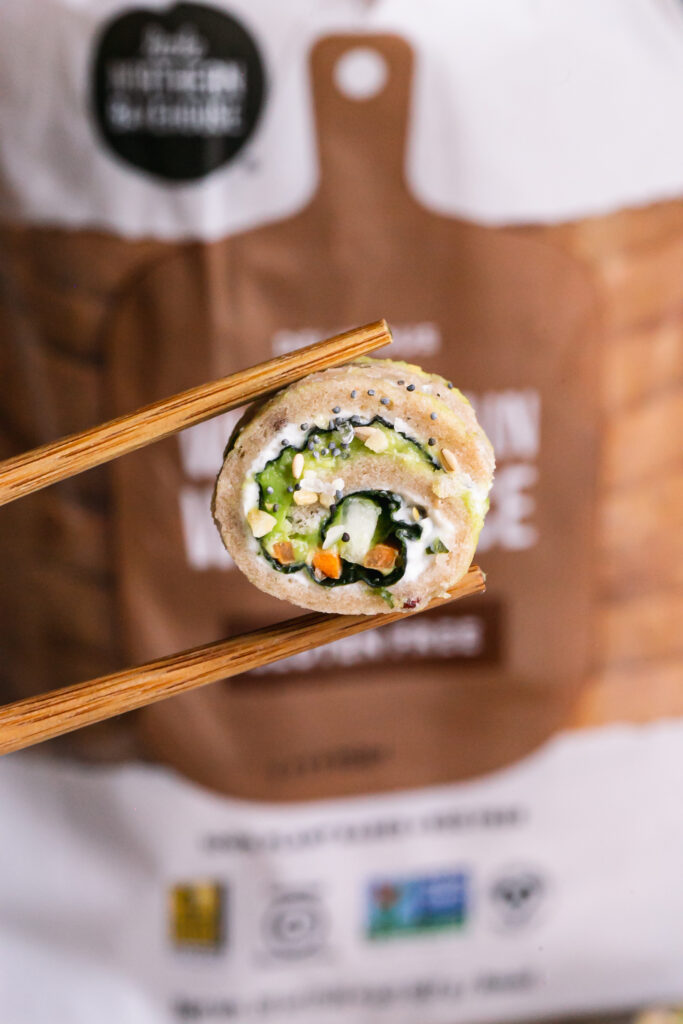 close up vertical image of a slice of veggie sandwich sushi held with chopsticks and a loaf of Little Northern Bakehouse whole grain bread in the background