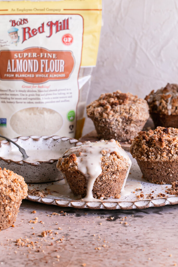 one iced cinnamon streusel muffin with other unfrosted muffins around it, a bowl of icing beside it and a bag of Bob's Red Mill blanced almond flour in the background
