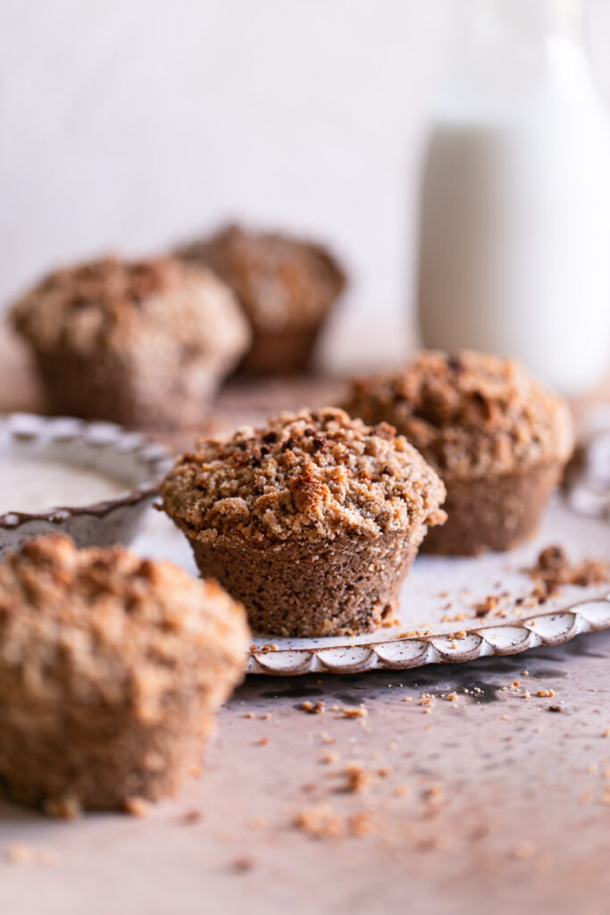unfrosted cinnamon streusel muffins with a bowl of icing beside it and a jug of milk in the background