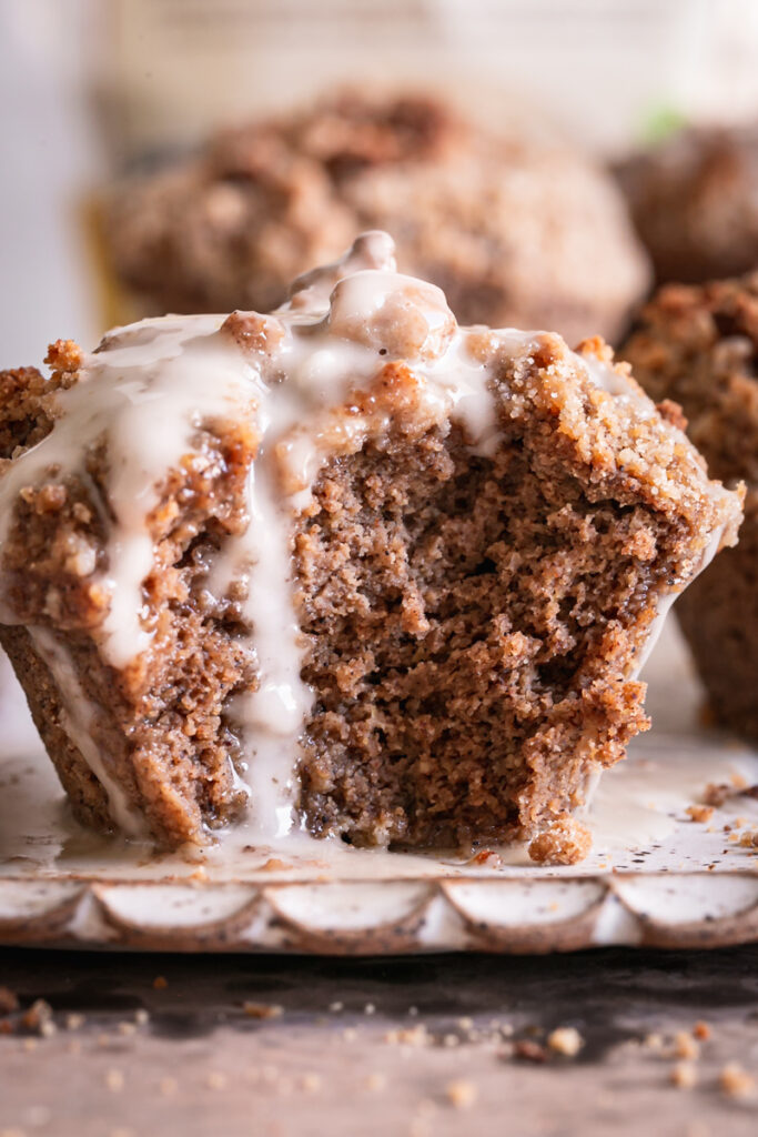 close up of a frosted cinnamon streusel muffin with a bite taken out of it