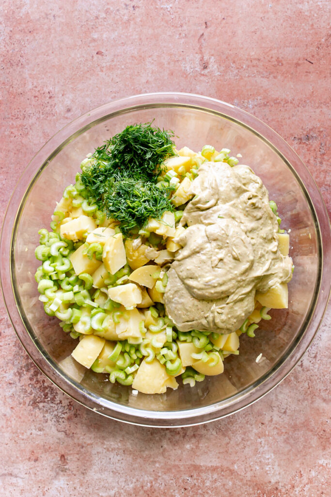 cooked potatoes, sliced celery, chopped dill, and smoked paprika dressing ingredients in a bowl