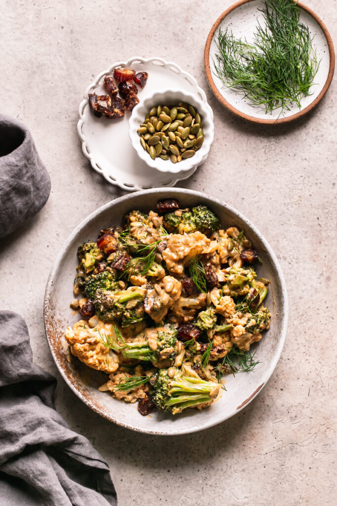 a bowl of tahini harissa cauliflower with a bowl of toasted pumpkin seeds, chopped dates, and fresh dill above it and a linen napkin on the side