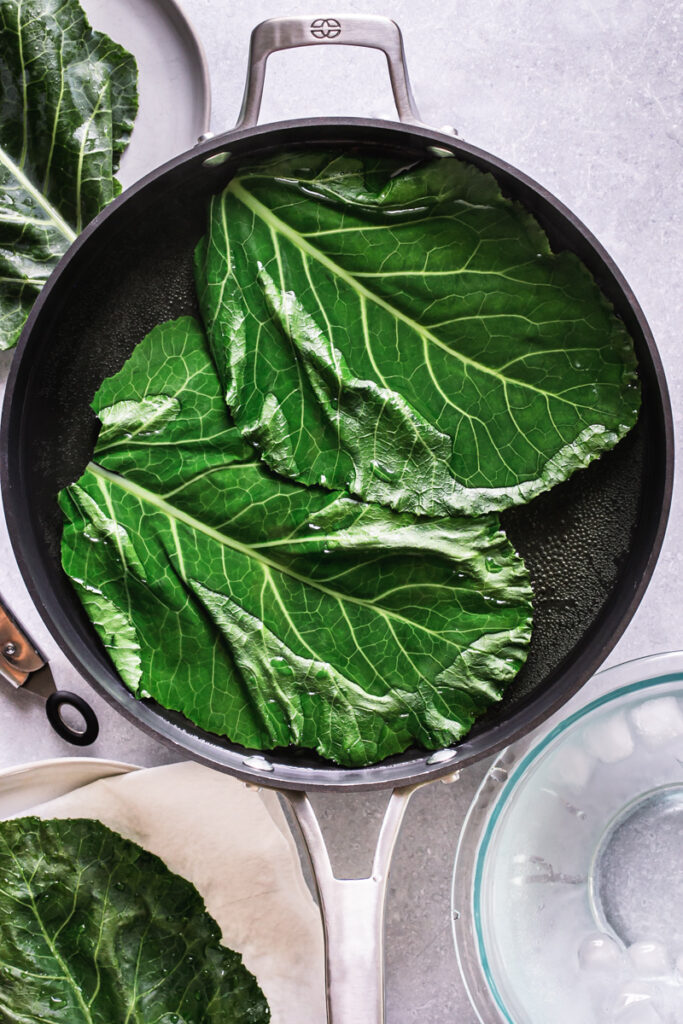 two collard wraps boiling in a skillet filled with hot water to blanch them with a bowl of ice water beside it