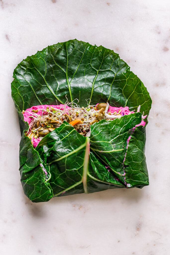 a half folded collard wrap filled with all of the fillings to show how to roll it