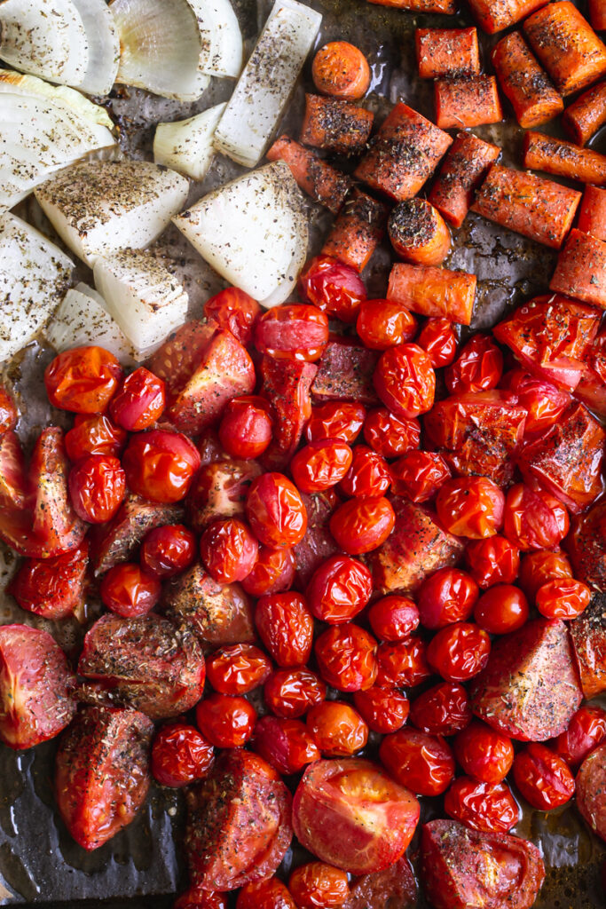 a tray of roasted tomatoes, carrots and onion