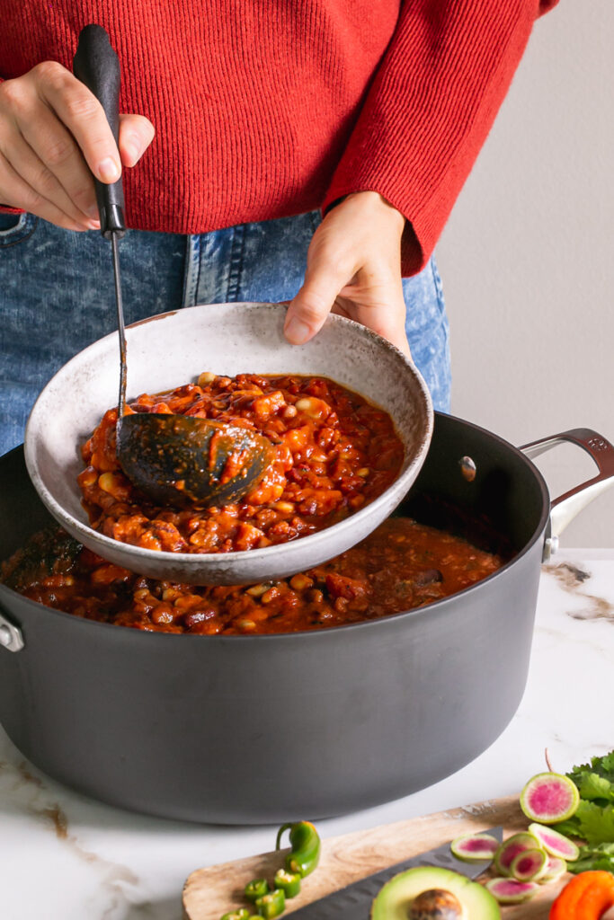 action shot of me serving out some chili from the pot into a bowl