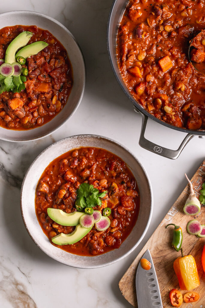 two bowls of vegan three bean harissa pumpkin chili with a Calphalon pot next to it and sliced produce for garnishes