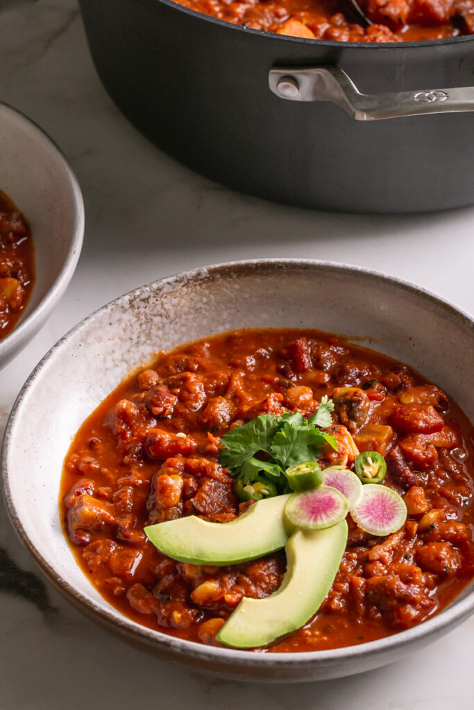 3/4 view of a bowl of chili with the calpalon pot in the back