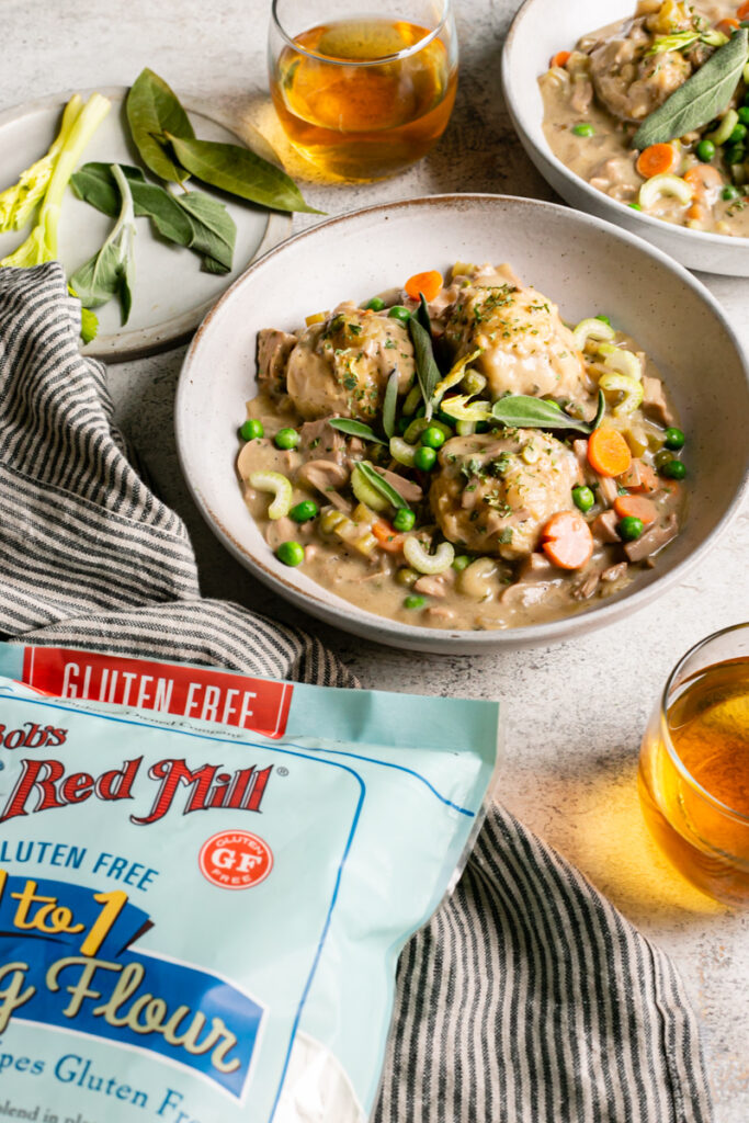 3/4 view of chicken and dumplings served in a bowl with two glasses of wine, and a bag of bob's red mill gluten-free 1:1 baking flour