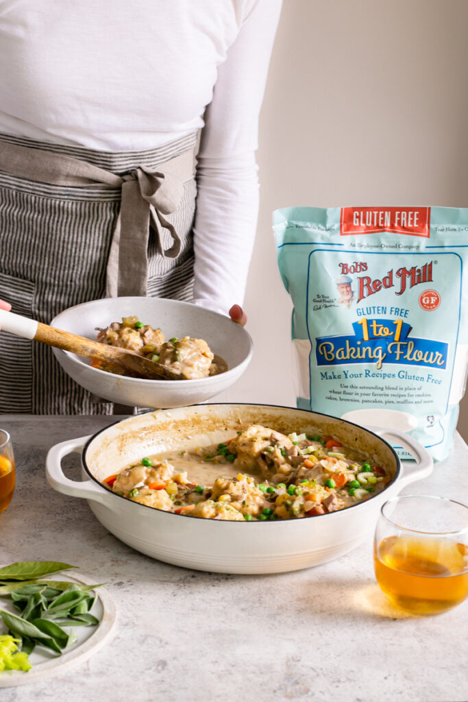 action shot of serving some chicken and dumplings into a bowl with a bag of Bob's Red Mill gluten-free 1:1 baking flour in the background