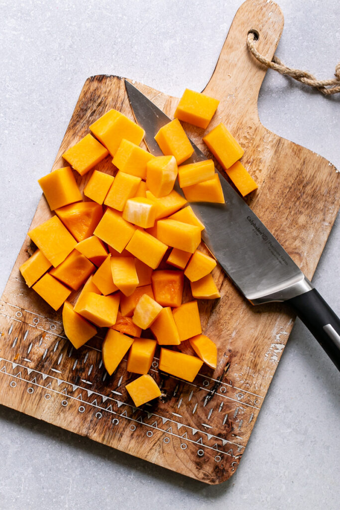 the entire butternut squash cut into chunks on a cutting board with the knife next to it
