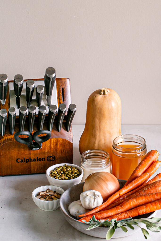Calphalon 15-piece knife block, a whole butternut squash, a jar of vegetable broth, a jar of plant milk, a bowl of roasted almonds, a bowl of toasted pumpkin seeds, a bowl of whole carrots, an onion, garlic, and sage