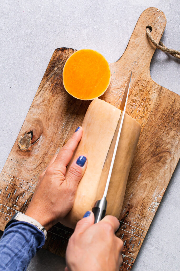 an action photo of slicing a butternut squash in half
