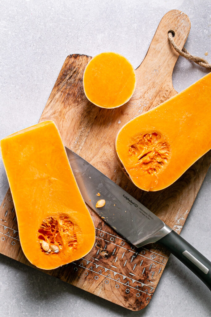 a butternut squash cut in half on a cutting board with the knife laying beside it