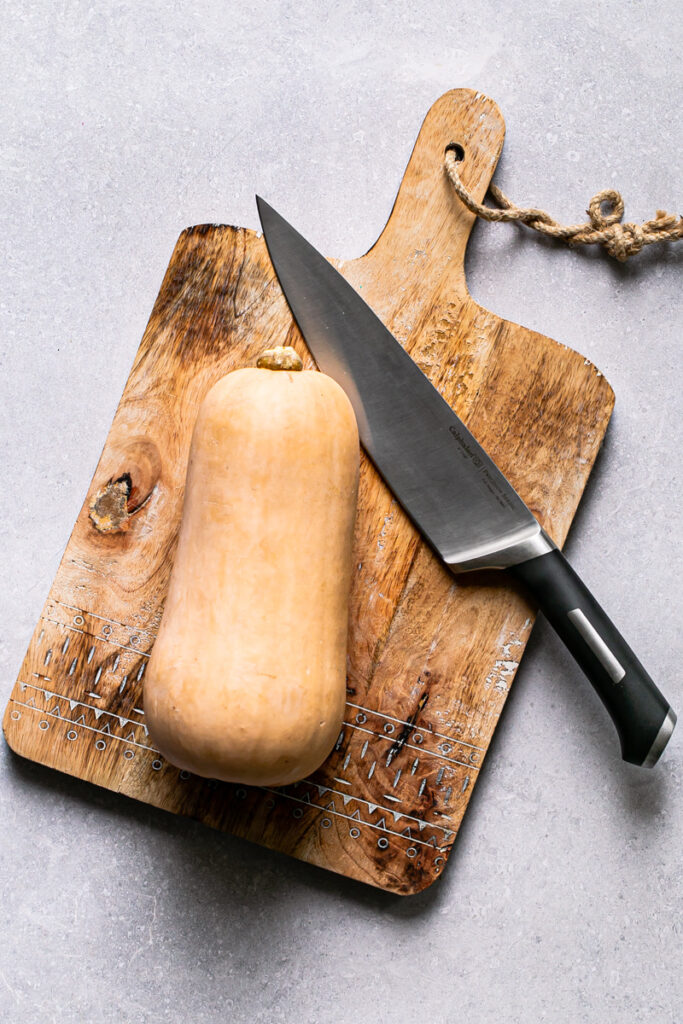 """a whole butternut squash on a cutting board with an 8"""" Calphalon chef knife"""