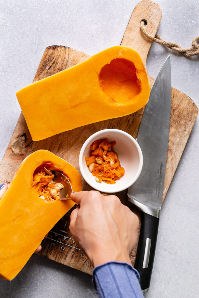 action shot of spooning out the butternut squash seeds with the Calphalon knife on the cutting board next to it